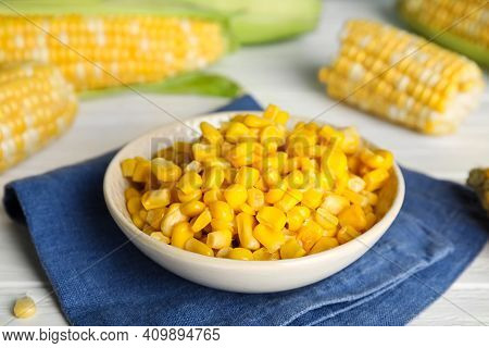 Tasty Sweet Corn Kernels In Bowl And Fresh Cobs On Table