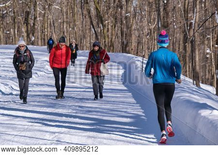 Montreal, Ca - 4 February 2021: People Walking Or Running On A Snowy Trail In Montreal\'s Mount Roya