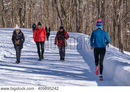 Montreal, Ca - 4 February 2021: People Walking Or Running On A Snowy Trail In Montreal's Mount Royal