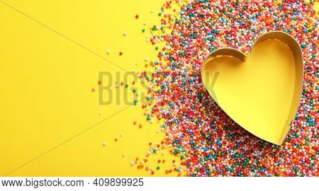 Heart Shaped Cookie Cutter And Sprinkles On Yellow Background, Flat Lay With Space For Text. Confect