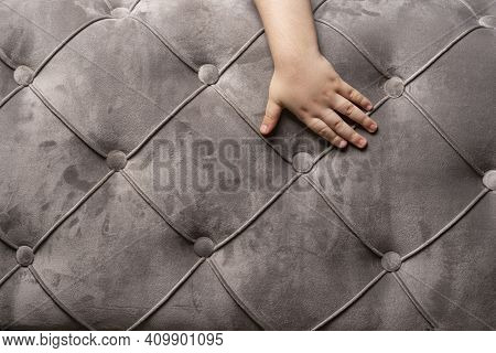 Gray Velvet Couch Texture Background With A Child Hand, Close Up Velvet Sofa Texture.