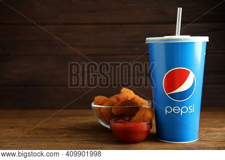Mykolaiv, Ukraine - February 16, 2021: Cup Of Pepsi, Chicken Nuggets And Dip Sauce On Wooden Table.