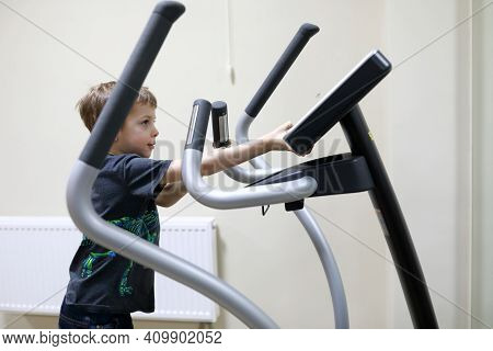 Child Exercising At Stride Treadmill In Gym