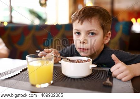 Child Has Breakfast In Restaurant