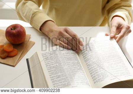 Woman With Holy Bible At White Table Indoors, Closeup. Great Lent Season