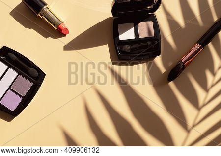 Decorative Cosmetics For Make-up And Sun Shadows From Tropical Leaf On Beige Background Flat Lay Top