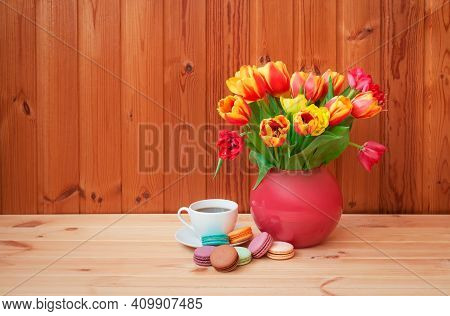 Colorful Tulips In Pink Vase  And Cup Of Coffee With Macaroons On Wooden Table. View With Copy Space