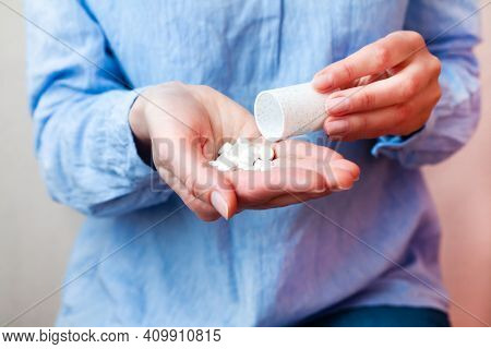 Woman In A Blue Blouse Pouring Pills From A Bottle Into Her Hand. Taking Antibiotic, Antidepressant