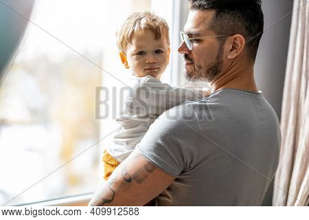Dad holding his child in his arms at home