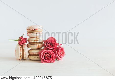 Tasty French Macaroons With Pink Roses On A White Wooden Background. Place For Text.