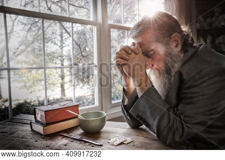 Old man with a beard saying grace and praying giving thanks over a simple meal, focus on man's face and sleeve