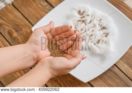 Home Gardening. Woman Holds Arugula Seeds In Her Palms. Preparation For Planting Arugula Seeds On A