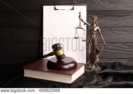 Lady Justice Or Justitia The Roman Goddess Of Justice. Statue On Brown Book With Judge Gavel On Blan