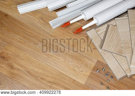 Set Of Items For Pvc Ceiling Indoor Works. Assembly Adhesive Bottles And Pvc Panels With Plastic Cor