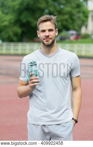 Man With Athletic Appearance Holds Bottle With Water. Athlete Drink Water After Training At Stadium