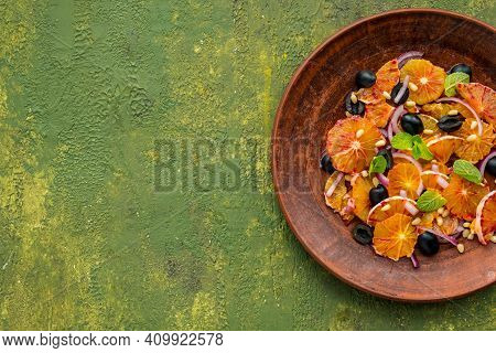 A Healthy Salad Of Sliced Bloody Oranges, Purple Onions, Olives And Pine Nuts With Olive Oil Dressin