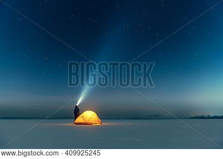 Tourist with flashlight near yellow tent lighted from the inside against the backdrop of incredible starry sky. Amazing night landscape. Tourists camp in snowy field. Travel concept