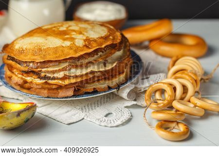 Pancake Day. A Stack Of Pancakes On A Painted Plate In Close-up And A Bunch Of Bagels. On A Light Wo