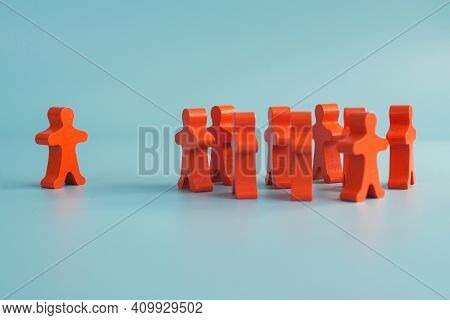 Wooden Figurines Of A Team And A Separate Person Or Opinion. Leadership Or Separation Concept.