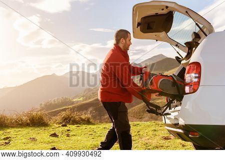 Mountain Person Leaving His Backpack In The Trunk Of His Off-road Car After A Day Of Trekking. Man L