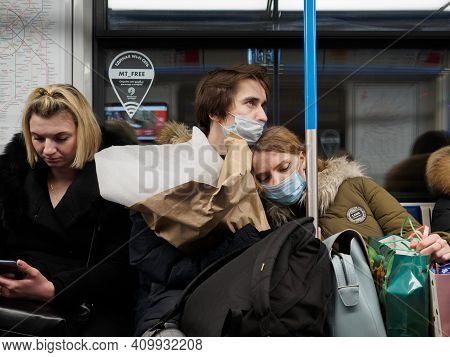 Moscow. Russia. February 25, 2021. In Love Girl And Guy In Protective Masks Sit In A Subway Car And