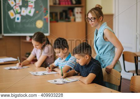 Teacher Helping School Kids Writing Test In Classroom. Education, Elementary School, Learning And Pe