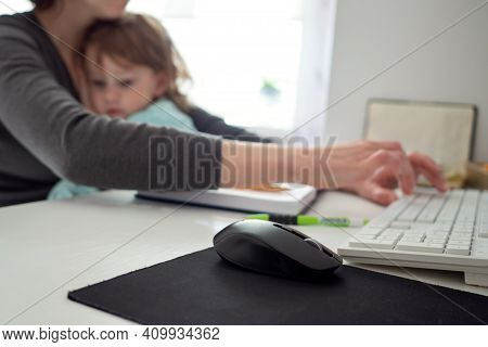 Mother Holding Girl Kid And Using Computer At Home With Selective Focus. Candid Authentic And Real L
