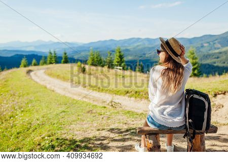 Trip To Carpathian Mountains. Woman Tourist Hiking And Relaxing Admiring Landscape Sitting On Bench