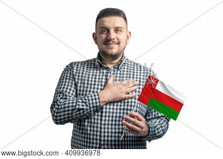 White Guy Holding A Flag Of Oman And Holds His Hand On His Heart Isolated On A White Background With