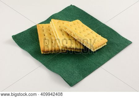 Cracker Sandwich With Tomato Basil Cheese Filling On Green Napkin On White Background