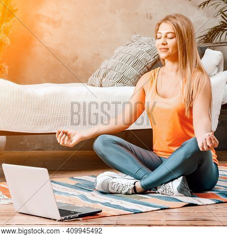 The Young Woman Goes In For Sports At Home. Cheerful Sportswoman With Blond Hair Meditates In Lotus