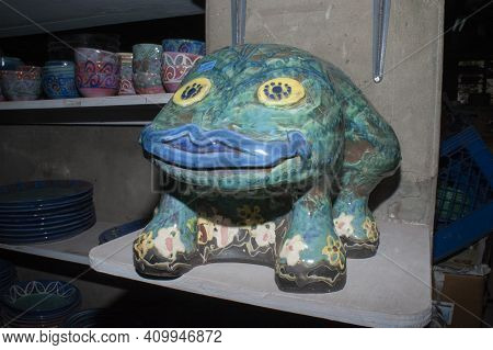 Caribbean Artisan Craft Pottery. Collectible Pottery Frog Next To Shelf Of Cups.