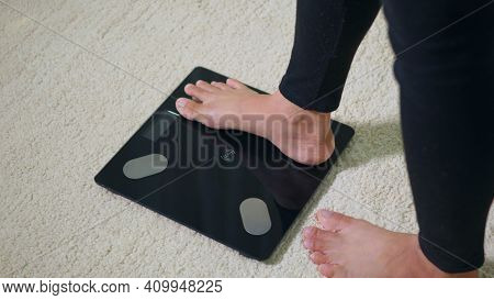 Asian Young Woman Leg Stepping Standing On Floor Electric Scales, Female Working Out At Home In Livi