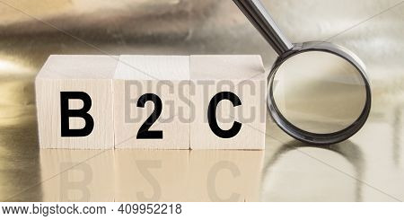 Three Wooden Cubes With Letters B2c Designation Business For A Client And A Magnifying Glass On A Go