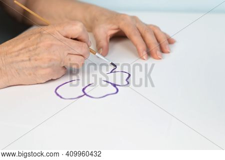 Female Hands Drawing A Flower With Watercolors, Close-up. Retired Woman's Hobby Concept. Selective F