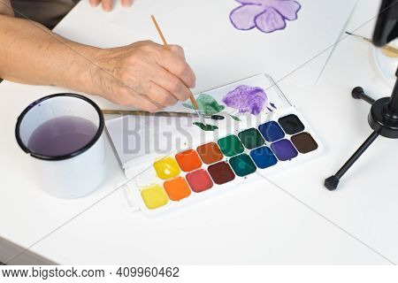 Female Elderly Hands Painting A Flower With Watercolors, Top View. Brush, Paints, Paper Lying On A W