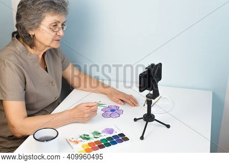 Retired Woman Watching An Online Drawing Course. An Elderly Woman In Glasses Paints Flowers With Wat