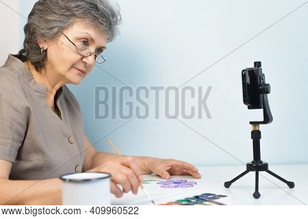Smiling Elderly Woman Watching Drawing Course Online. Pensioner In Glasses Painting Flowers With Wat