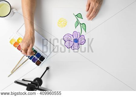 Female Elderly Hands Paint A Flower With Watercolors Indoors, Top View. Smartphone, Paints, Brushes