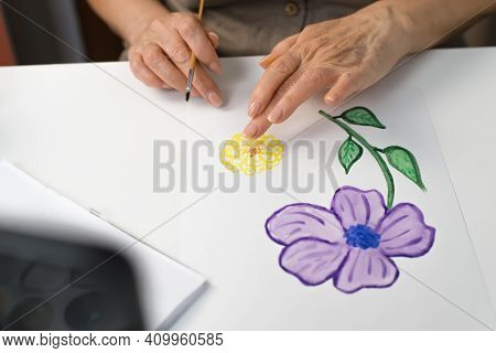 Woman's Hands Painting A Flower With Watercolors, Close-up. Retirement Hobby Concept. Selective Focu