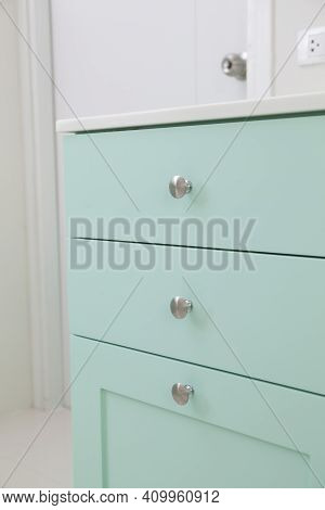 Close Up Of Kitchen Cabinets With Metal Pulls Or Knobs On The Doors.
