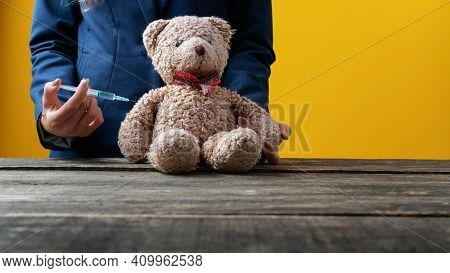 Closeup Of A Medical Doctor Vaccinating A Teddy Bear Toy In A Conceptual Image.