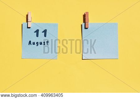 August 11. 11th Day Of The Month, Calendar Date. Two Blue Sheets For Writing On A Yellow Background.