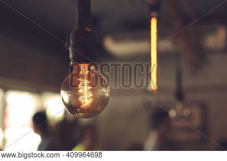 Close-up Of Incandescent Light Bulbs Hanging In The Dark Room. Decorative Antique Edison Light Bulbs