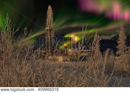 Polar Night. Winter Landscape With A Drilling Rig In The Northern Oil And Gas Field. In The Backgrou