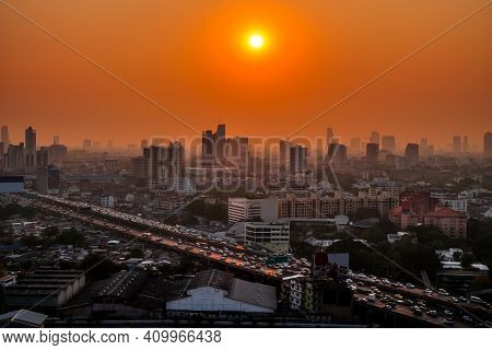 Aerial View Of The Modern Buildings Finance And Highway At Sunset Of Bangkok City, Thailand. The Car