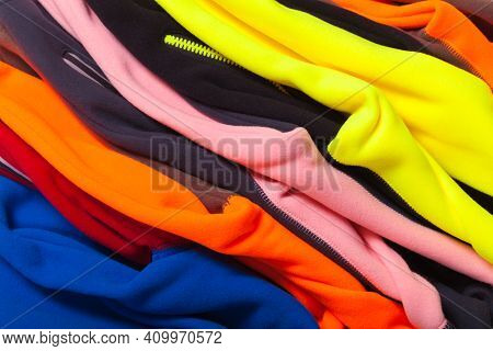 Pile Of Colorful Fleece Jackets, Close Up Photo With Selective Focus