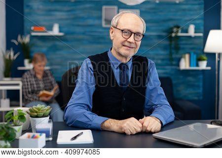 Portrait Of Senior Man Sitting At Desk Office Looking At Camera. Elderly Man Entrepreneur In Home Wo