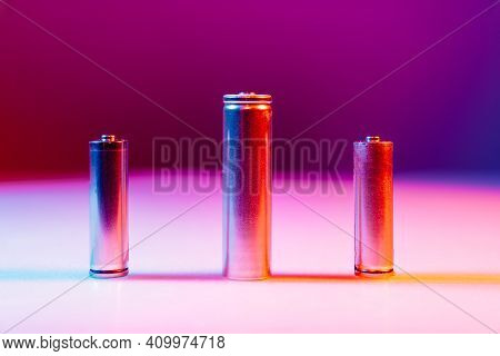 Aa And 8650 Li-ion Silver Batteries On Illuminated By Multicolored Light