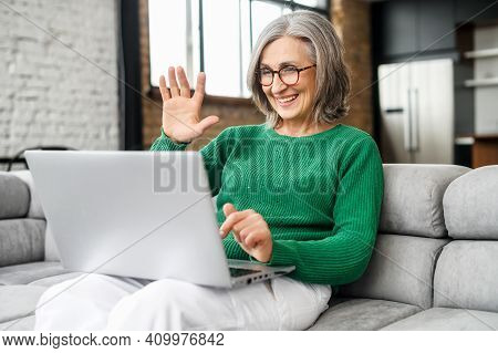 Young Good-looking Senior Mature Woman Is Using A Laptop For Video Connection, Recording A Message,